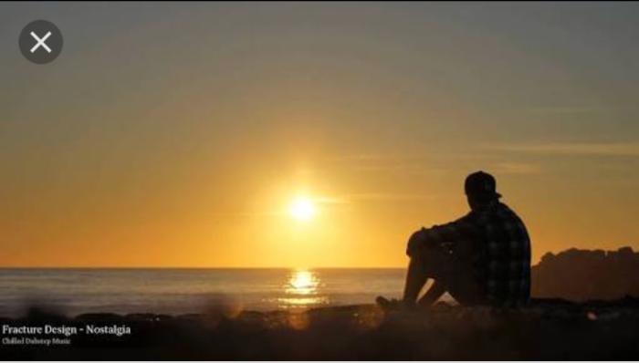 Sunset at beach guy sitting alone reflecting