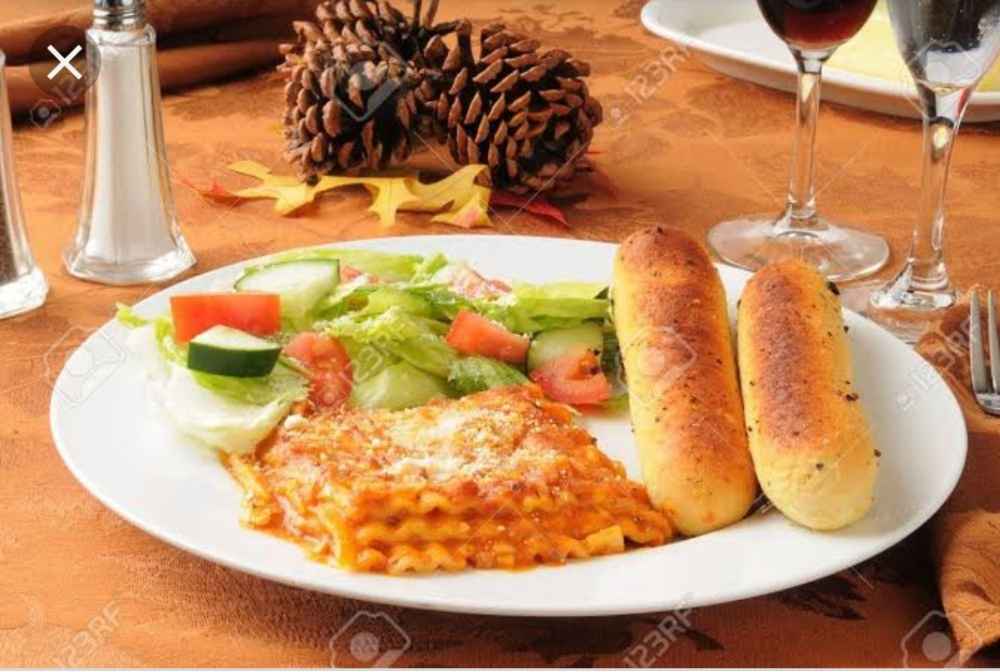 Lasagne served with bread sticks, salad and wine on a wooden table.