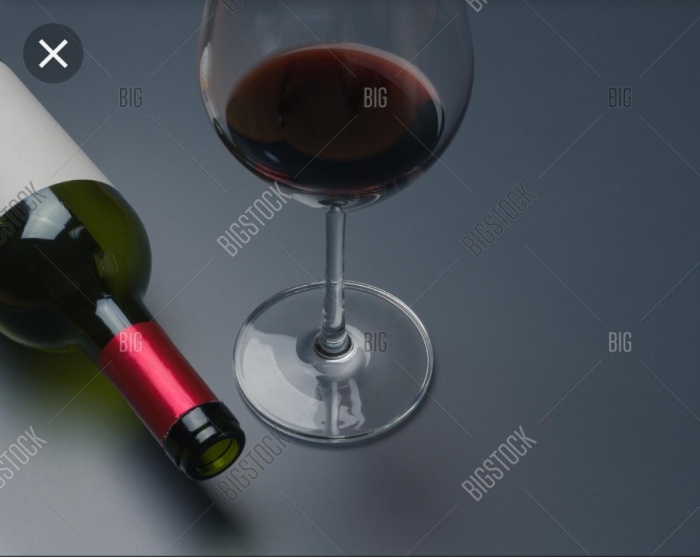 An empty bottle of wine with a wine glass