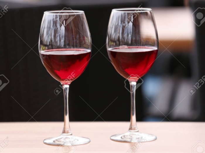 Two half filled glasses of red wine on a wooden table