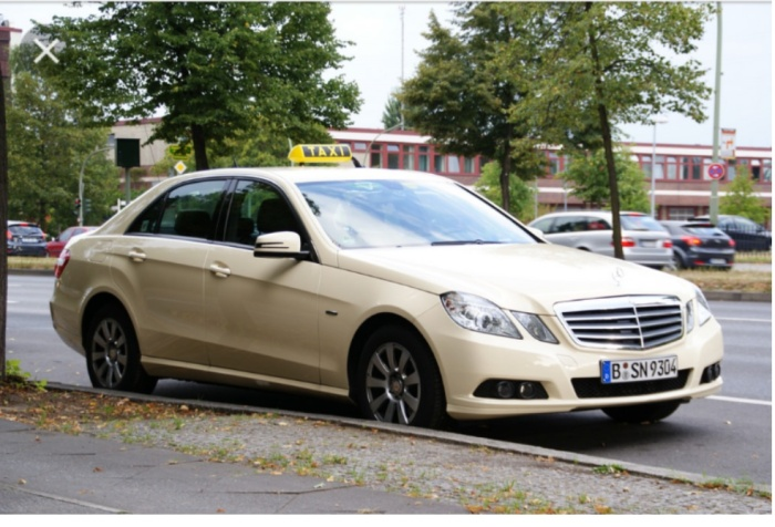 A cream coloured Mercedes Benz taxi parked at the curb
