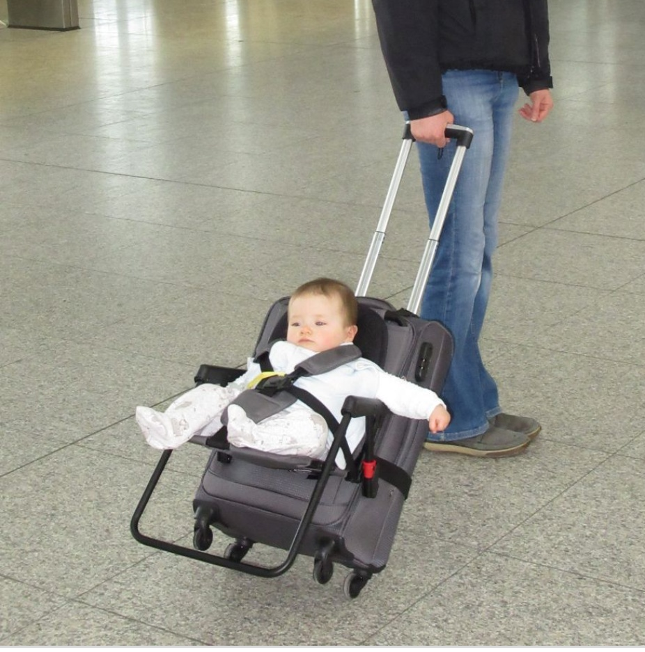 Baby girl Emma Geller-Greene strapped on to a luggage trolley