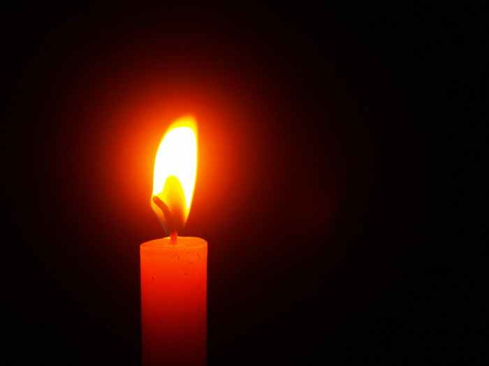 A lit candle in a dark background. Middle of the night. Hope in life