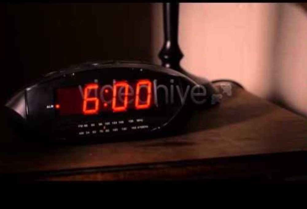An alarm clock displaying 6 am in Ross Geller's bedroom