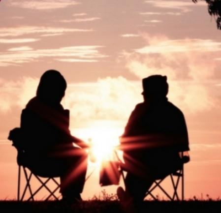 एक मुलगा व मुलगी सायंकाळी सूर्यास्त एकमेकांसोबत बसलेले. नातं, संबंध. A man and a woman sitting together under the evening setting sun shadowed. New leaf in relationship