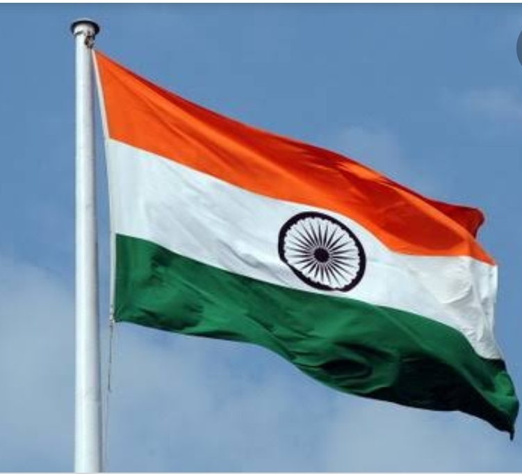Indian Tricolour national flag furling against clear blue sky